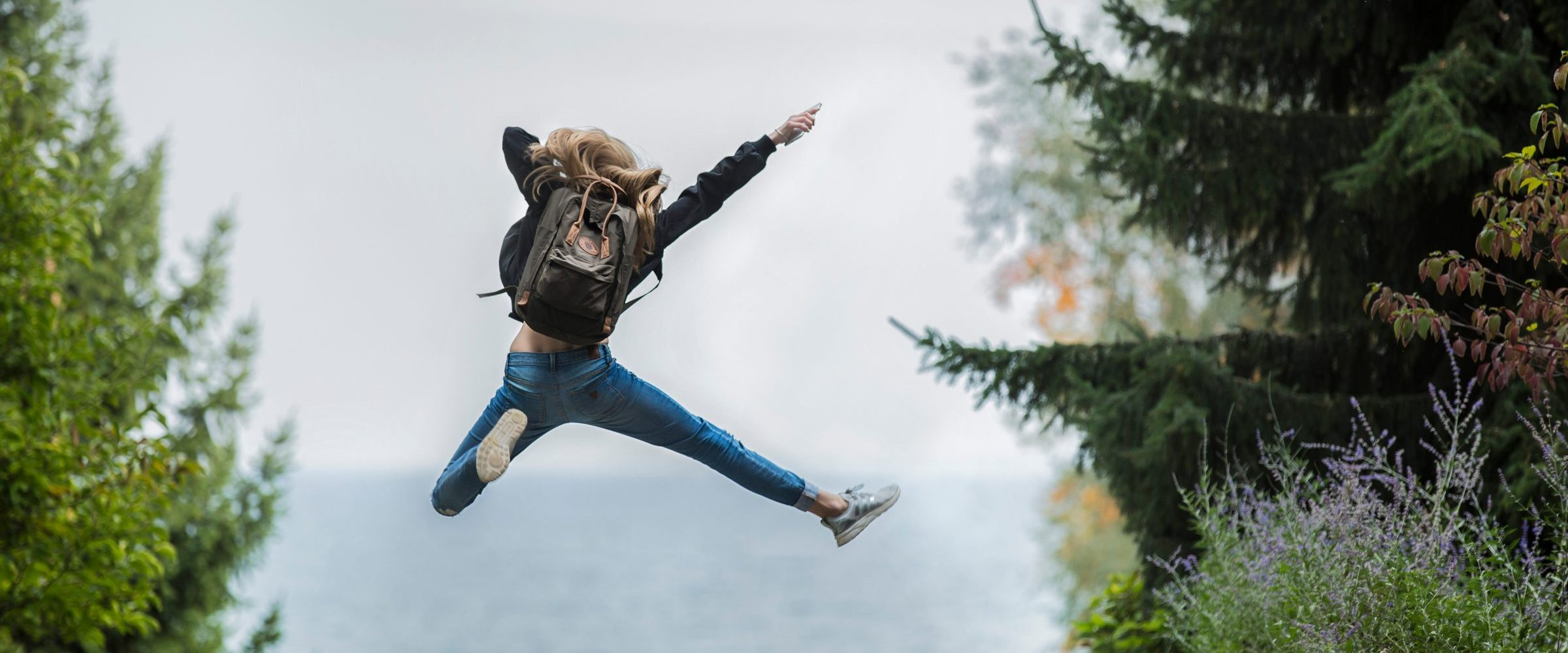 canva-woman-jumping-wearing-green-backpack